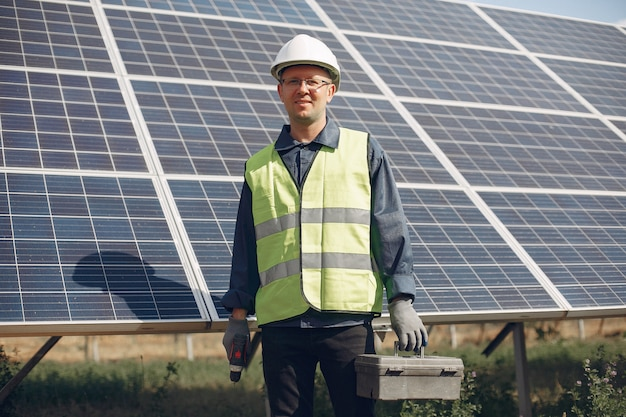 Mężczyzna w białym hełmie blisko panelu słonecznego
