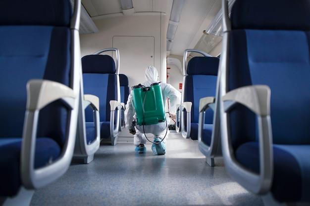 Mężczyzna w białym kombinezonie ochronnym dezynfekujący i dezynfekujący wnętrze pociągu metra, aby powstrzymać rozprzestrzenianie wysoce zaraźliwego wirusa koronowego
