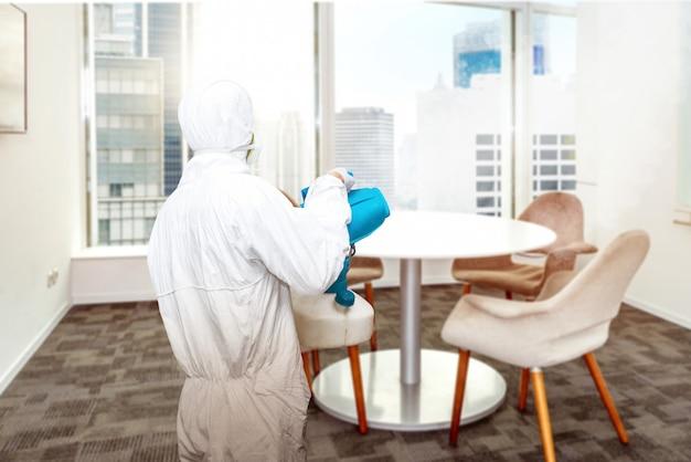 Mężczyzna w białym kombinezonie ochronnym rozpylającym środek dezynfekujący w pomieszczeniu biurowym