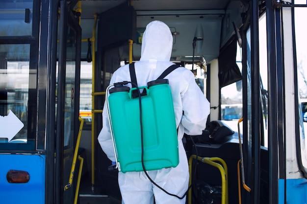 Mężczyzna w białym kombinezonie ochronnym ze zbiornikiem wchodzącym do autobusu, aby spryskać środek dezynfekujący z powodu globalnej pandemii wirusa koronowego