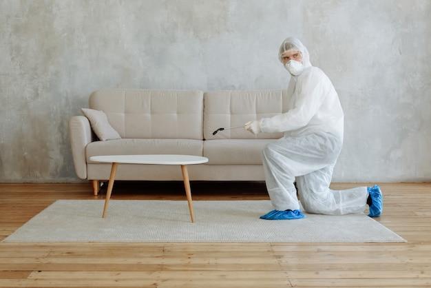 Mężczyzna w białym kombinezonie świadczy usługę dezynfekcji mieszkania przed wirusami i koronowirusem covid-19