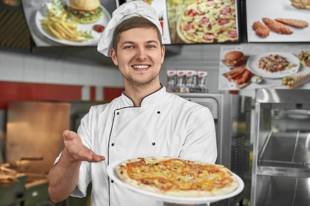 Mężczyzna w białym mundurze, oferujący klientom smaczną pizzę