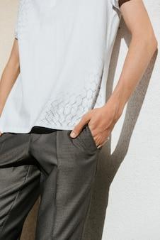 Mężczyzna w białym polo i szare spodnie pozuje na ulicy, aby reklamować odzież męską.