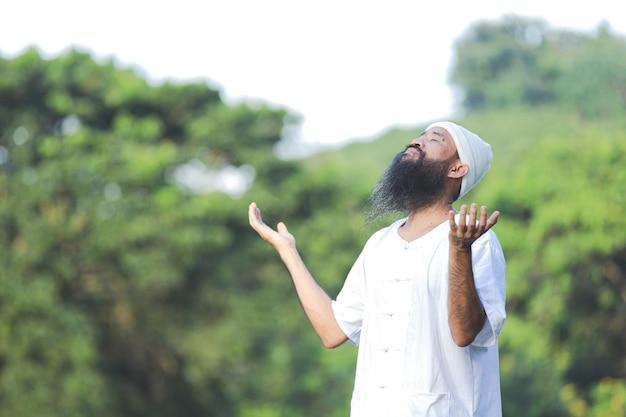 Mężczyzna w białym stroju medytuje w przyrodzie
