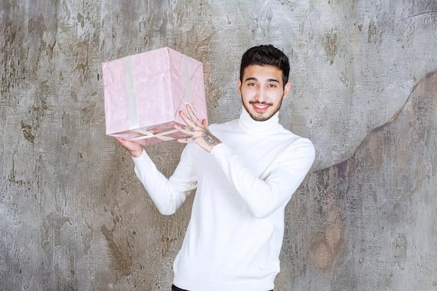 Mężczyzna w białym swetrze trzyma fioletowe pudełko owinięte wstążką.