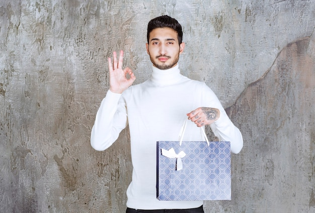 Mężczyzna w białym swetrze trzyma niebieską torbę na zakupy i pokazuje pozytywny znak ręki.