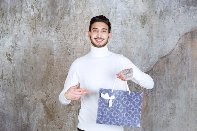 Mężczyzna w białym swetrze trzyma niebieską torbę na zakupy.