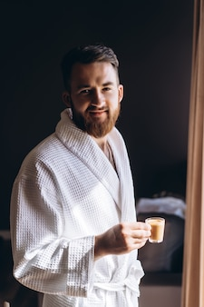 Mężczyzna w białym szlafroku z kubkiem kawy w dłoni.