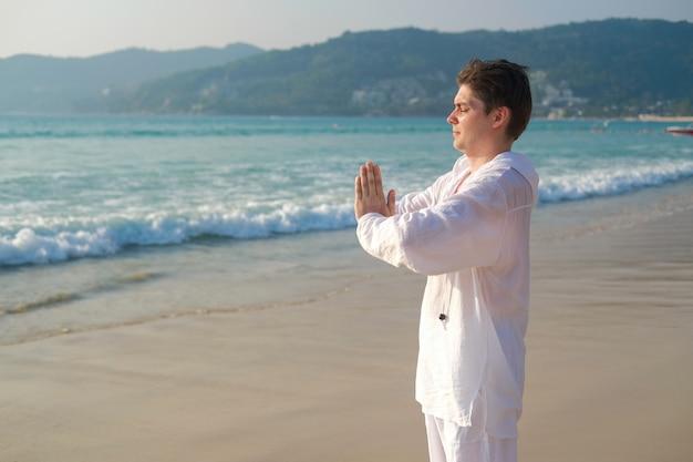 Mężczyzna w białym ubraniu trzyma ręce w geście modlitwy i praktykuje medytację jogi