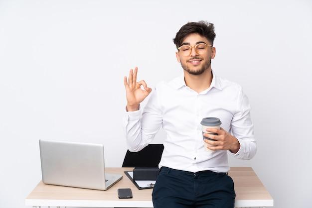 Mężczyzna w biurze na białym tle w pozie zen