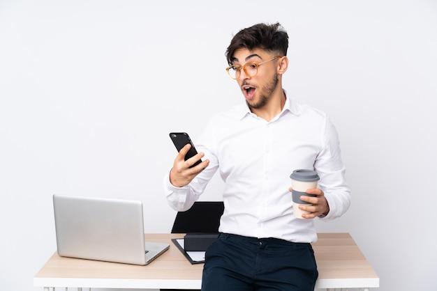 Mężczyzna w biurze odizolowywającym na biel ścianie trzyma kawę zabrać i wiszącą ozdobę