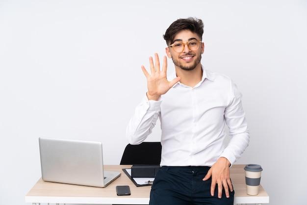 Mężczyzna w biurze pokazuje pięć palcami