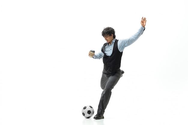 Mężczyzna w biurze ubrania, grając w piłkę nożną lub piłkę nożną z piłką na białej przestrzeni. niezwykły wygląd dla biznesmena w ruchu, akcji. sport, zdrowy tryb życia.