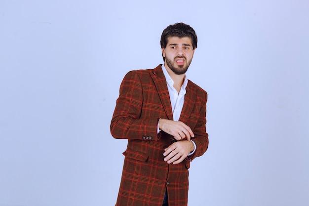 Mężczyzna w biznesową kurtkę, wskazując na swój czas.