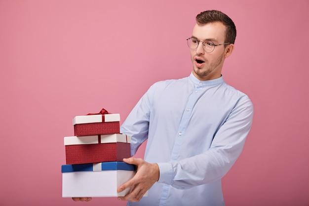 Mężczyzna w błękitnej koszula trzyma prezenty w pudełkach w rękach