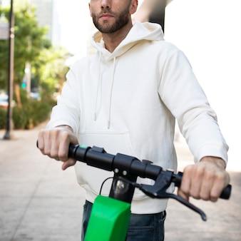 Mężczyzna w bluzie z kapturem jedzie na hulajnodze elektrycznej