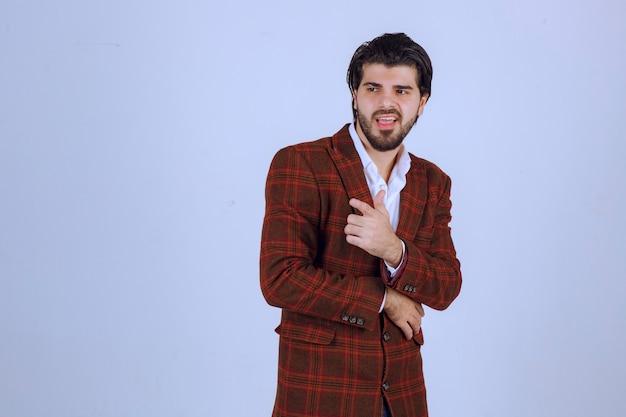 Mężczyzna w brązowej kraciastej kurtce, wskazując na kogoś z przodu.