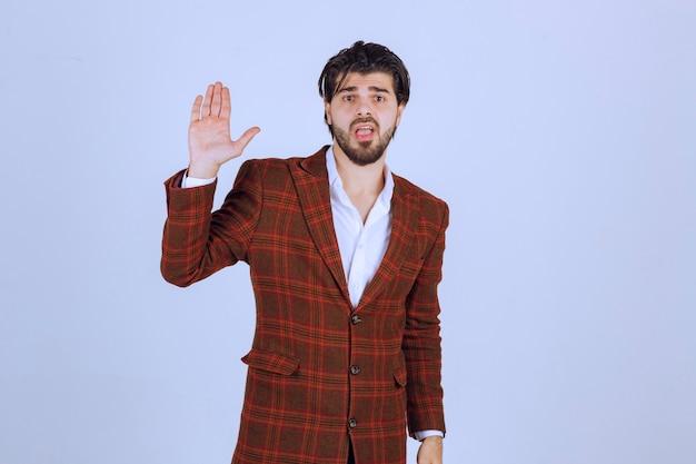 Mężczyzna w brązowej kurtce podnosząc rękę na uwagę.
