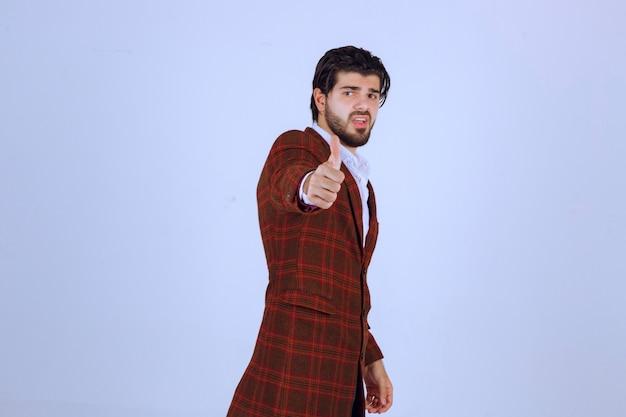 Mężczyzna w brązowej kurtce pokazuje kciuk znak.