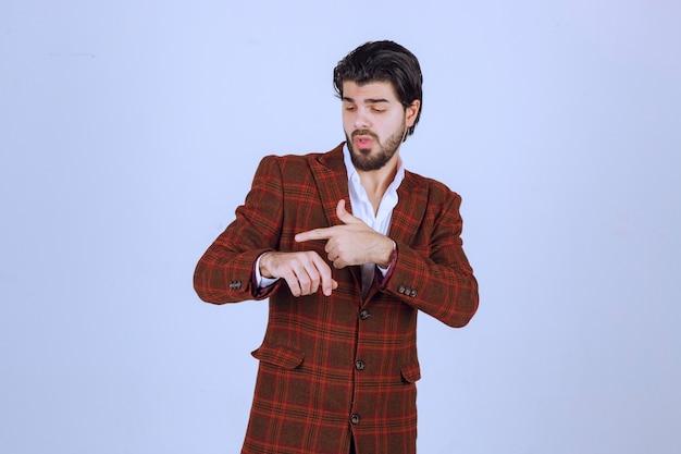 Mężczyzna w brązowej kurtce sprawdza swój czas.