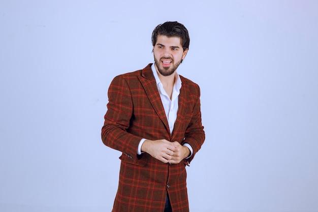 Mężczyzna w brązowej kurtce stoi i obserwuje bez reakcji.