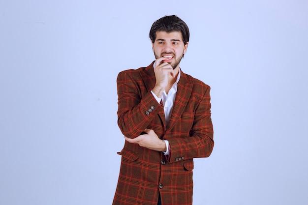 Mężczyzna w brązowej kurtce wygląda na zamyślonego, zagubionego i zagubionego.