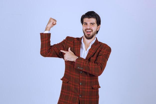 Mężczyzna w brązowej marynarce trzymający pięści i pokazujący swoją moc.