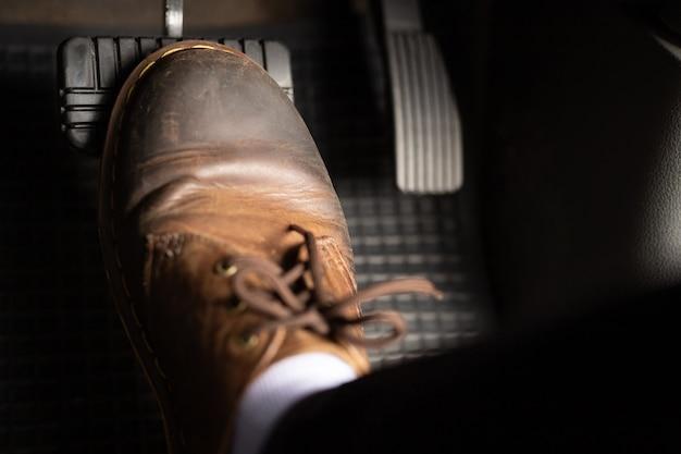 Mężczyzna w brązowych skórzanych butach nadepnie na hamulce samochodu.