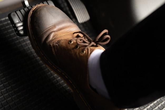 Mężczyzna w brązowych skórzanych butach wciska pedał gazu.