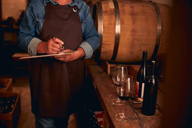 Mężczyzna w brązowym fartuchu stojący ze schowkiem i długopisem obok beczki wina. butelki i szklanki na stole