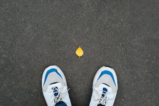 Mężczyzna w butach stoi na asfalcie z pojedynczym opadłym żółtym liściem jesienią, widok z góry. koncepcja cześć październik, sezon jesienny.