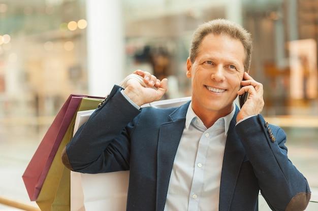 Mężczyzna w centrum handlowym. pewny siebie dojrzały mężczyzna trzymający torby na zakupy i rozmawiający przez telefon komórkowy, stojąc w centrum handlowym
