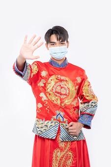 Mężczyzna w cheongsam i masce pokazuje, że osoby, które nie noszą masek, nie mogą robić zakupów podczas księżycowego nowego roku.