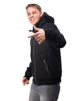 Mężczyzna w ciemnej bluzie gestem ręki