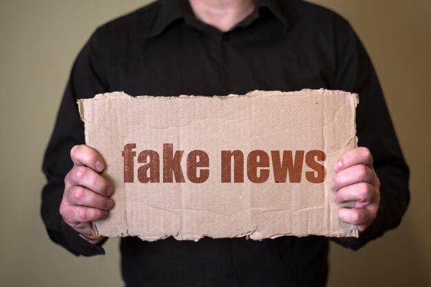 Mężczyzna w ciemnej koszuli trzymający kartkę z tekstem fake news