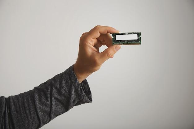 Mężczyzna w ciemnoszarej koszulce z długim rękawem, trzymając chip pamięci bez etykiety na białym tle, z bliska