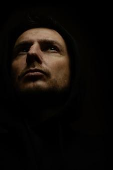 Mężczyzna w ciemnym pokoju w kapturze jak zabójca. efekt artystyczny ziarna i szumu.