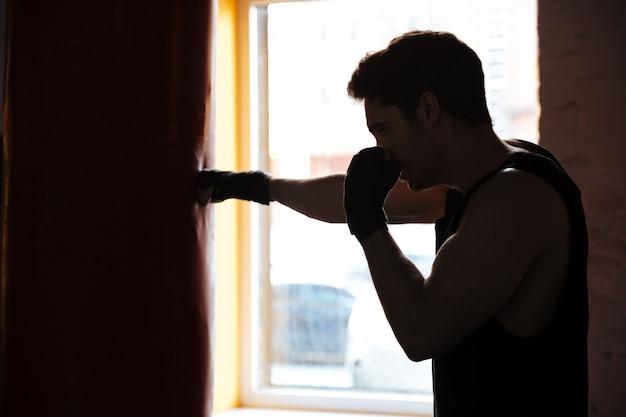 Mężczyzna w cieniu kopiąc worek treningowy