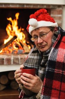 Mężczyzna w ciepłej odzieży z kubkiem gorącego napoju na tle ognia