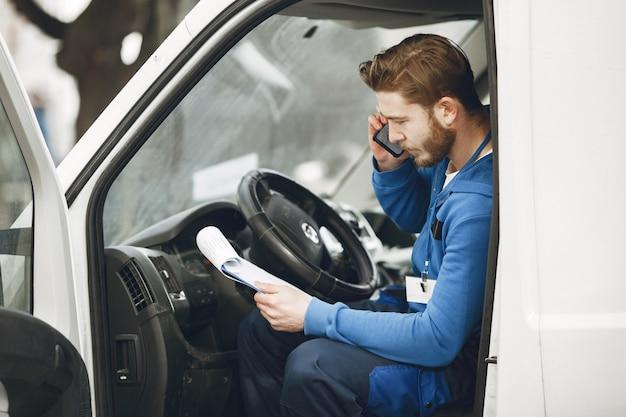 Mężczyzna w ciężarówce. facet w mundurze dostawczym. człowiek ze schowkiem.