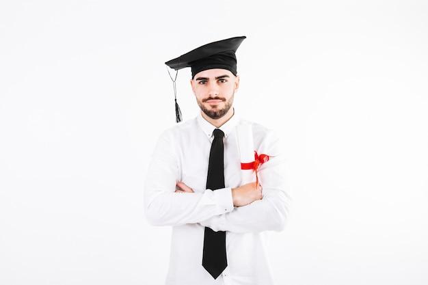 Mężczyzna w czapce akademickiej z krzyżami ramion