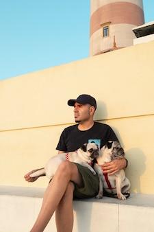 Mężczyzna w czapce i okularach przeciwsłonecznych z psami o zachodzie słońca obok latarni morskiej aveiro w portugalii