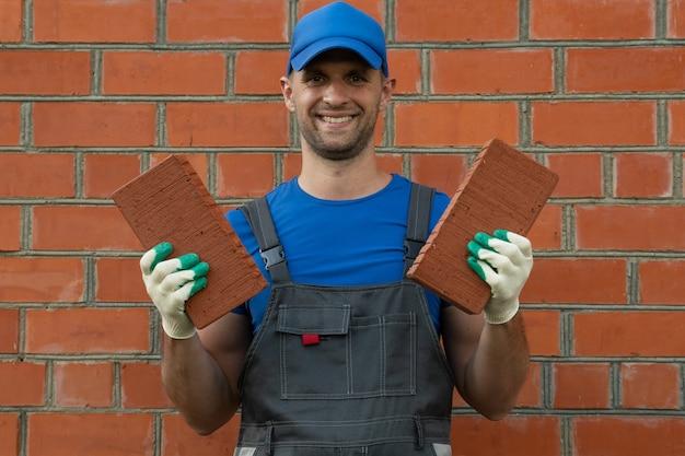 Mężczyzna w czapce i rękawiczkach pokazuje cegłę przed kamerą w koncepcji budowlanej