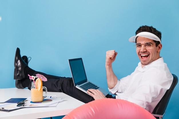 Mężczyzna w czapce i ubraniach biurowych śmieje się podczas pracy i picia koktajlu na niebieskiej przestrzeni. facet trzyma laptopa.