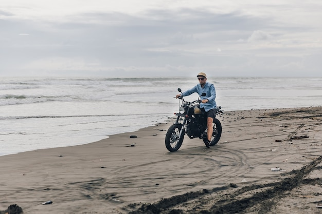 Mężczyzna w czapce, jazda motocyklem na plaży. moto cross dirtbiker na plaży o zachodzie słońca na bali. młody hipster mężczyzna cieszący się wolnością i aktywnym trybem życia, bawiąc się na wycieczce motocyklowej.