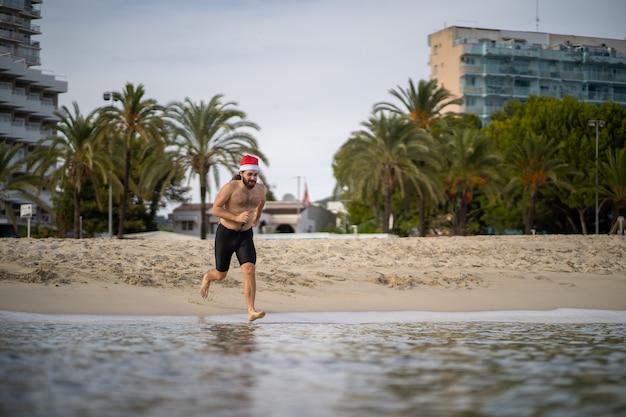 Mężczyzna w czapce świętego mikołaja biegnie od brzegu do wody, aby pluskać się w niej w czapce świętego mikołaja