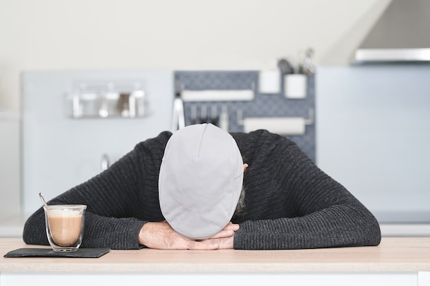 Mężczyzna w czapce z opuszczoną głową w dłoniach na stole ze szklanką kawy i mleka