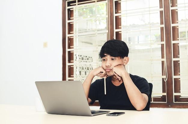 Mężczyzna w czarnej azjatyckiej koszulce siedział przed laptopem z zawiedzionym wyrazem twarzy