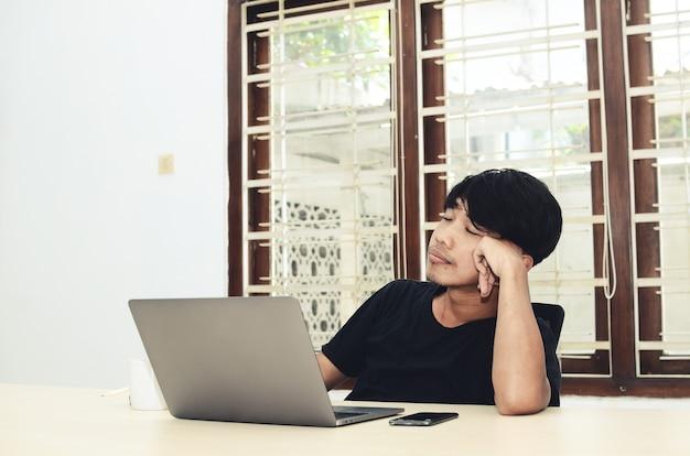 Mężczyzna w czarnej azjatyckiej koszulce siedział przed laptopem ze smutnym wyrazem twarzy