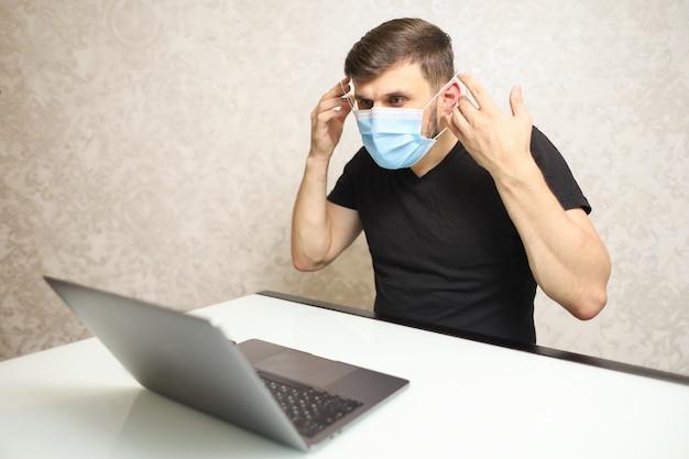 Mężczyzna w czarnej koszulce na białym biurko pracuje na laptopie